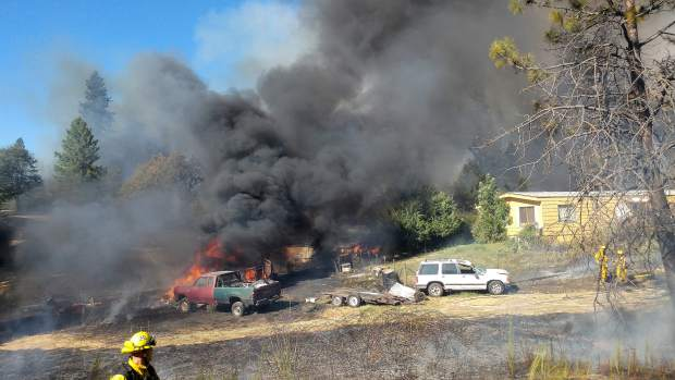 A vehicle is fully engulfed in flames and black smoke behind Peterson's Corner in North San Juan near where Wednesday's wildland fire began.