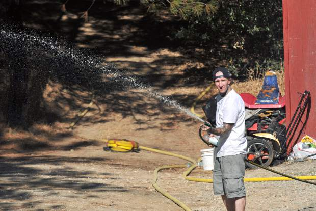 A North San Juan resident uses a garden hose to help protect his property from any stray embers Wednesday.