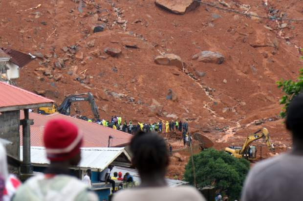 In this photo taken on Monday and provided by IFRC, Red Cross volunteers dig for survivors at the scene of heavy flooding and mudslides in Regent, just outside of Sierra Leone's capital Freetown. The Red Cross estimates that 600 people are still missing as the death toll from massive mudslides in Sierra Leone's capital is certain to rise above 300. An official says the local mortuary is