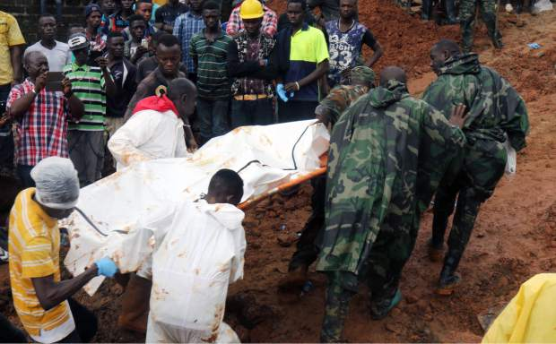 In this photo taken on Monday, Aug. 14, 2017 and provided by IFRC, Red Cross volunteers remove bodies from the scene of heavy flooding and mudslides in Regent, just outside of Sierra Leone's capital Freetown. The Red Cross estimates that 600 people are still missing as the death toll from massive mudslides in Sierra Leone's capital is certain to rise. Authorities say more than 300 were killed in and around Freetown following heavy rains. Many victims were trapped under tons of mud as they slept. An official says the local mortuary is