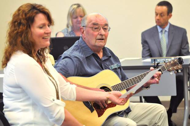 Melissa Parrett (left) and board of education member Bob Altieri perform a song written in Holly Hermansen's honor during Tuesday night's board meeting.