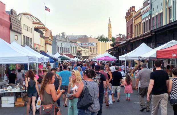 Folks mingle at the corner of Mill and Main Streets in downtown Grass Valley's historic district during the final Thursday Night Market of the summer.