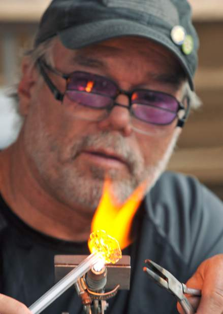 Grass Valley's Jeff Petty of Gold Bug Glass Blowers, works on venetian miniatures during the Thursday Night Market.