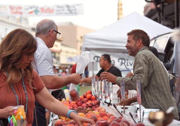 Kamal Jit (right) of Yuba County's Dhillon Farms, assists customers at Grass Valley's Thursday Night Market.