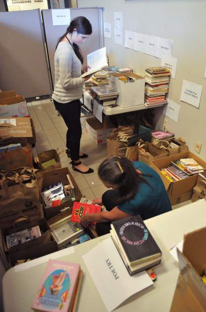 County Administrative Analyst Taylor Wolfe (left) and Deputy Clerk to the Board of Supervisors Leila Loomis, work on sorting hundreds of donated books Wednesday.