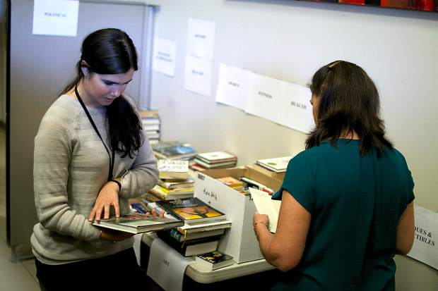 Nevada County's Taylor Wolf (left) and Lelia Loomis sort through hundreds of books this week in the Eric Rood Center in anticipation of the annual book sale which begins on Monday and runs through October 27.
