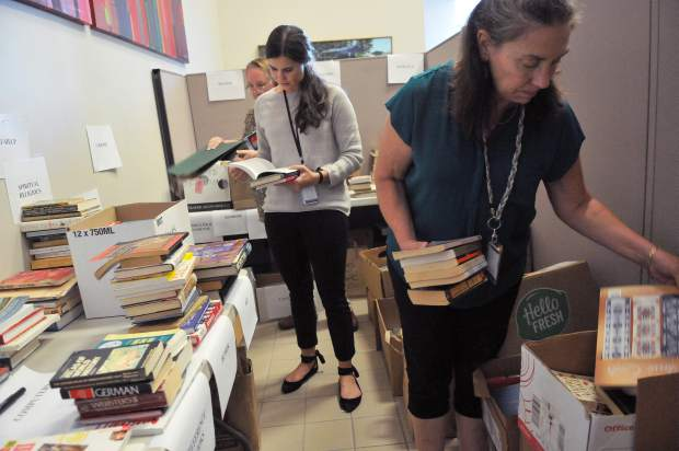 Nevada County Deputy Clerk to the Board of Supervisors Lelia Loomis (from front), Administrative Analyst Taylor Wolfe, and Brenda Austin with the Community Development Agency, took time out of their schedules to help receive and sort books for the county's annual book sale.