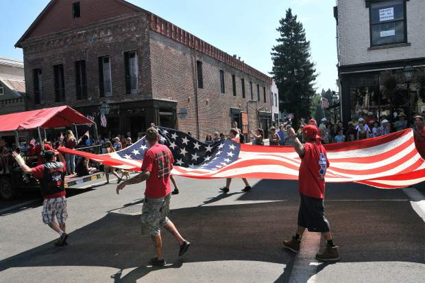 Members of the local E.Clampus Vitus hold a large United States flag as they march down Broad Street during the annual Constitution Day parade.