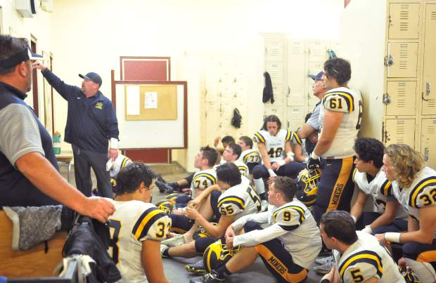 Nevada Union head coach Dennis Houlihan goes over some play changes with his team in the locker room at half time when the Miners were trailing the Del Oro Eagles 15-7.