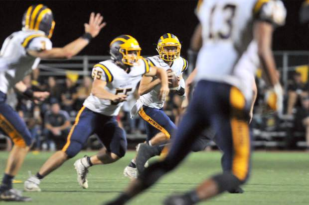 Nevada Union quarterback Owen Dal Bon (center) keeps an eye on his options as a play ensues during the Miners' matchup against the Del Oro Eagles Friday in Loomis.