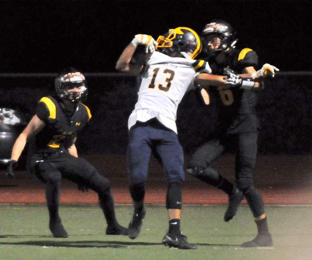 Nevada Union tight end Cameron Dallago is pulled down in the endzone by Del Oro's Johnny Guzman for a Miner touchdown.