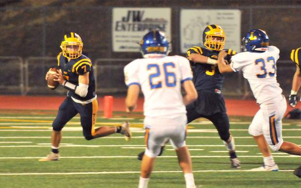 Nevada Union quarterback Owen Dal bon looks for an open receiver during Friday night's 23-22 loss to the visiting Zebras.
