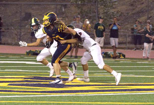 Nevada Union's Justin Houlihan tries for extra yards after making a catch during a game against Placer at Hooper Stadium Friday. The Miners topped the Hillmen, 43-16.