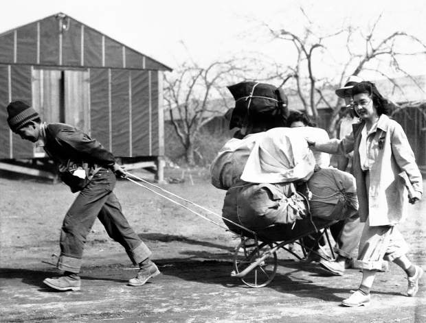 In this June 19, 1942 file photo, Japanese evacuees move into a war relocation authority center in Manzanar, Calif. Roughly 120,000 Japanese immigrants and Japanese-Americans were sent to desolate camps that dotted the West.