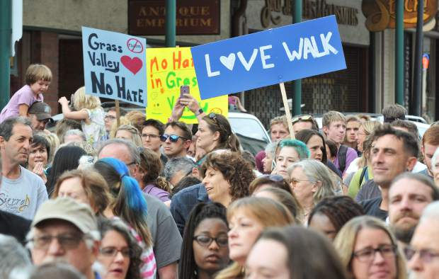Folks carry signs as they march down Mill Street during the Love Walk organized after a community member experienced a racial injustice earlier this week.
