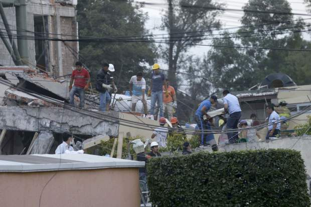 Volunteers and rescue personnel work on the remains of a collapsed primary school after a 7.1 earthquake struck Mexico City, Tuesday, Sept. 19, 2017. Rescue workers are working frantically in an attempt to find children they believe are trapped under the rubble. (AP Photo/Marco Ugarte)