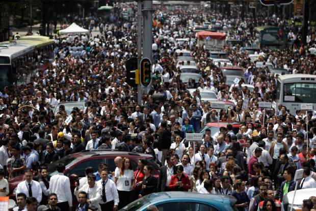 People evacuated from office buildings gather in Reforma Avenue after an earthquake in Mexico City, Tuesday Sept. 19, 2017. A powerful earthquake jolted central Mexico on Tuesday, causing buildings to sway sickeningly in the capital on the anniversary of a 1985 quake that did major damage.(AP Photo/Rebecca Blackwell)