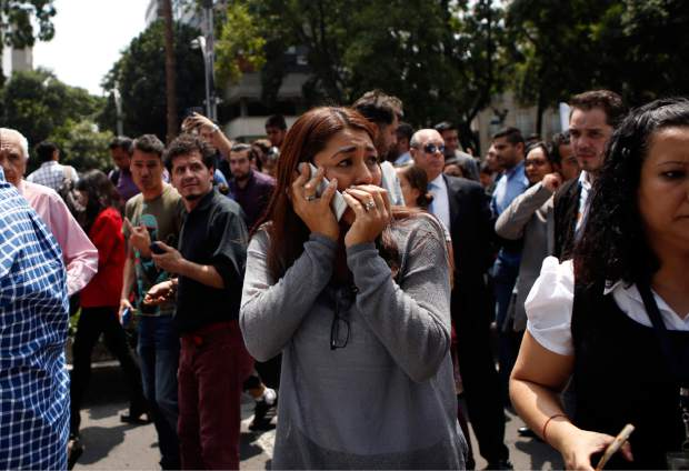 A woman speaks on her cell phone as people evacuated from office building gather in Reforma Avenue after an earthquake in Mexico City, Tuesday Sept. 19, 2017. A powerful earthquake jolted central Mexico on Tuesday, causing buildings to sway sickeningly in the capital on the anniversary of a 1985 quake that did major damage.(AP Photo/Rebecca Blackwell)