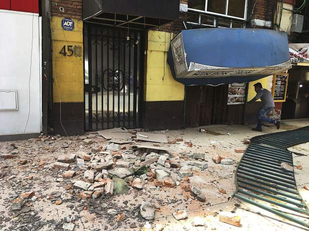 A man enters a damaged building after an earthquake in Mexico City, Tuesday, Sept. 19, 2017. A powerful earthquake jolted central Mexico on Tuesday, cracking building facades and scattering rubble on streets in the capital on the anniversary of a devastating 1985 quake. (AP Photo/Eduardo Verdugo)