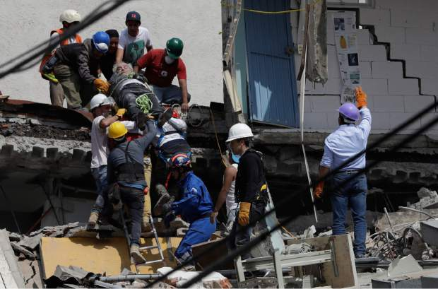 An injured man is pulled out of a building that collapsed during an earthquake in the Roma Norte neighborhood of Mexico City, Tuesday, Sept. 19, 2017. A powerful earthquake jolted central Mexico on Tuesday, causing buildings to sway sickeningly in the capital on the anniversary of a 1985 quake that did major damage. (AP Photo/Rebecca Blackwell)