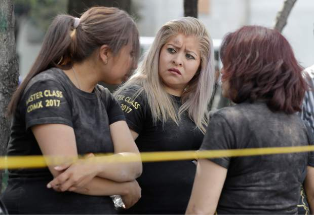 Women are covered in dust after making it out of a building that collapsed after an earthquake in the Roma neighborhood of Mexico City, Tuesday, Sept. 19, 2017. A powerful earthquake jolted central Mexico on Tuesday, causing buildings to sway sickeningly in the capital on the anniversary of a 1985 quake that did major damage. (AP Photo/Rebecca Blackwell)