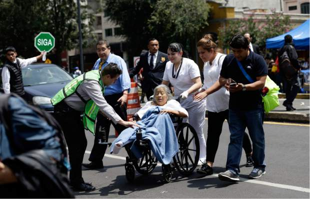 A woman in a wheelchair is evacuated from a clinic as people gather along Paseo de la Reforma Avenue after an earthquake in Mexico City, Tuesday Sept. 19, 2017. A powerful earthquake jolted central Mexico on Tuesday, causing buildings to sway sickeningly in the capital on the anniversary of a 1985 quake that did major damage. (AP Photo/Marco Ugarte)