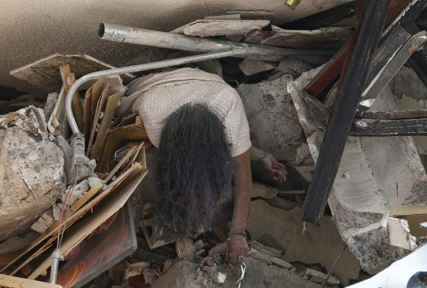 GRAPHIC CONTENT - The body of woman hangs crushed by a collapsed building in the neighborhood of Roma Norte, in Mexico City, Tuesday, Sept. 19, 2017. Throughout Mexico City, rescuer workers and residents dug through the rubble of collapsed buildings seeking survivors following a 7.1 magnitude quake. (AP Photo/Marco Ugarte)
