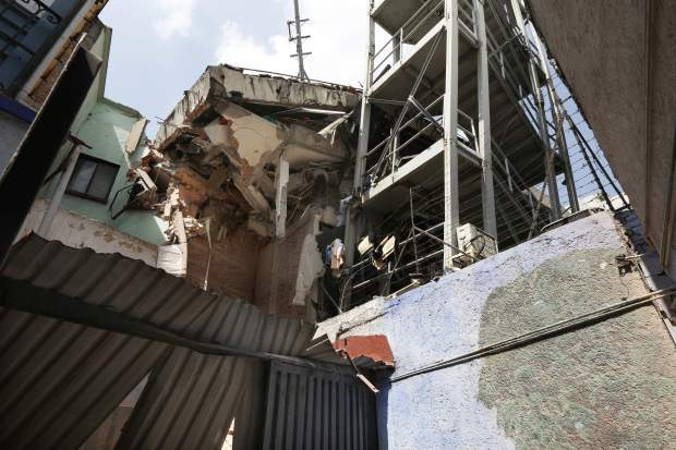 The body of woman hangs crushed by a collapsed building in the neighborhood of Roma Norte, in Mexico City, Tuesday, Sept. 19, 2017. Throughout Mexico City, rescuer workers and residents dug through the rubble of collapsed buildings seeking survivors following a 7.1 magnitude quake. (AP Photo/Marco Ugarte)