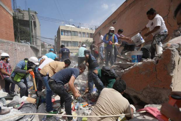 Rescue workers and volunteers search for survivors at the Ninos Heroes neighborhood in Mexico City, Tuesday Sept. 19, 2017. A magnitude 7.1 earthquake has stunned central Mexico, killing at ore than 100 people as buildings collapsed in plumes of dust. (AP Photo/Miguel Tovar)