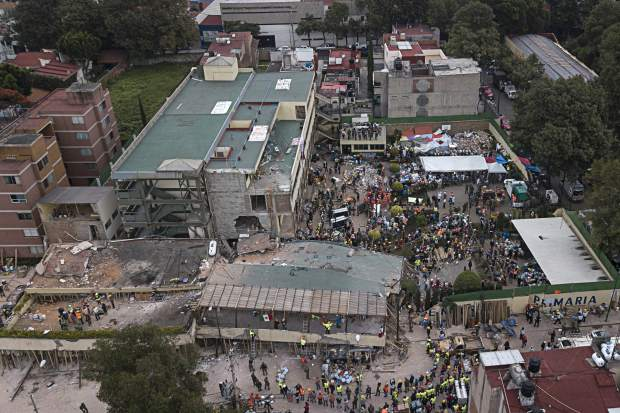 Volunteers and rescue workers search for children trapped inside the Enrique Rebsamen school, collapsed by a 7.1 earthquake in southern Mexico City, Wednesday Sept. 20, 2017. Police, firefighters and ordinary Mexicans dug frantically through the rubble of collapsed schools, homes and apartment buildings early Wednesday, looking for survivors of Mexico's deadliest earthquake in decades as the number of confirmed fatalities stood at 217. One of the most desperate rescue efforts was at the Enrique Rebsamen school, where a wing of the three-story building collapsed into a massive pancake of concrete slabs. (AP Photo/Miguel Tovar)