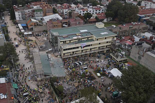 Volunteers and rescue workers search for children trapped inside the Enrique Rebsamen school, collapsed by a 7.1 earthquake in southern Mexico City, Wednesday Sept. 20, 2017. One of the most desperate rescue efforts was at the school, where a wing of the three-story building collapsed into a massive pancake of concrete slabs. The school's rooftops and facade bore messages that called for silence and for no helicopters to flyover, so as not to drown out the sounds of anyone who may trapped in the rubble. (AP Photo/Miguel Tovar)