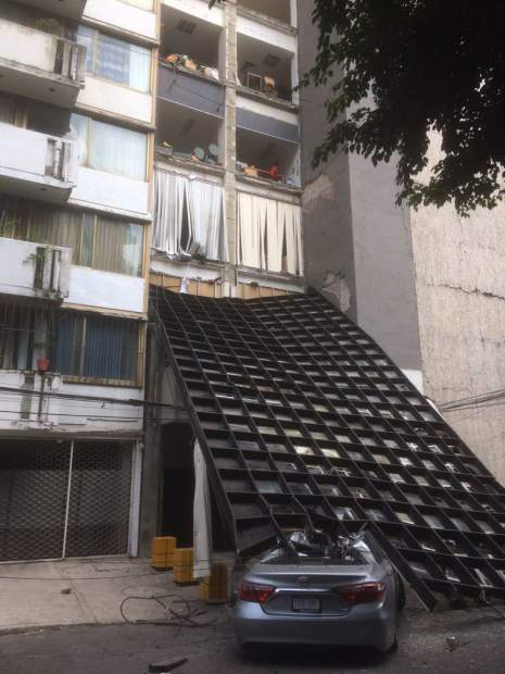 In this photo provided by Jean-Louis Bambuck, an exterior metal part of a building, where a Jewish museum is housed, lays on top of a car that was parking when it fell, after an earthquake in the Condesa neighborhood of Mexico City, Tuesday, Sept. 19, 2017. The driver was able to exit the car. A powerful earthquake jolted central Mexico on Tuesday, causing buildings to sway sickeningly in the capital on the anniversary of a 1985 quake that did major damage. (Jean-Louis Bambuck via AP)
