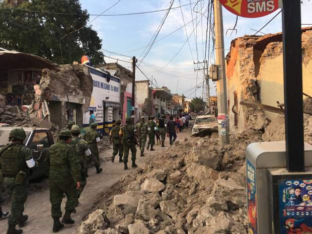 Soldiers walk past piles of rubble from buildings felled by a 7.1 earthquake, in Jojutla, Morelos state, Mexico, Tuesday, Sept. 19, 2017. The earthquake stunned central Mexico, killing at least 139 people as buildings collapsed in plumes of dust. (AP Photo/Carlos Rodriguez)
