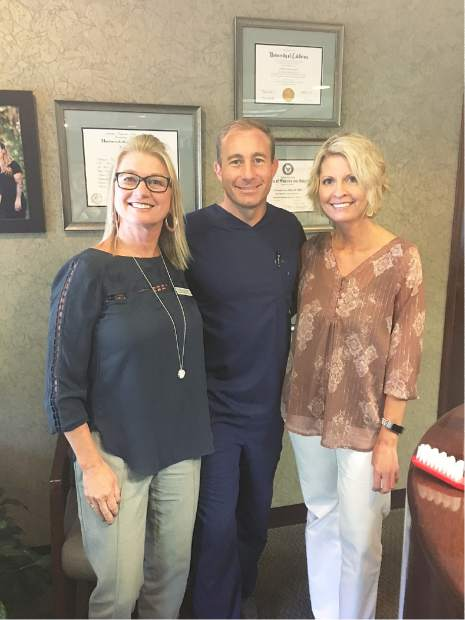 D.r Miller, new owner of Gawley Dental Care, posing for a picture with two of his front office assistants, Debby Coffey (left) and Regina Propps (right).
