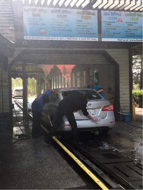 Suds Bros. Car Wash employees David Kazy, Fox Stubbs, and Drew Stevens working hard to get this vehicle squeaky clean.