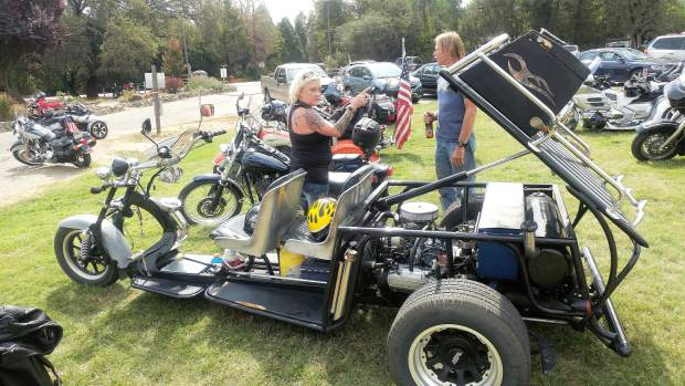 Trayci and Tim Haines of Penn Valley stand near a custom built trike equipped with a Subaru engine on display at Saturday's Welcome Home Vets event held at Western Gateway Park.