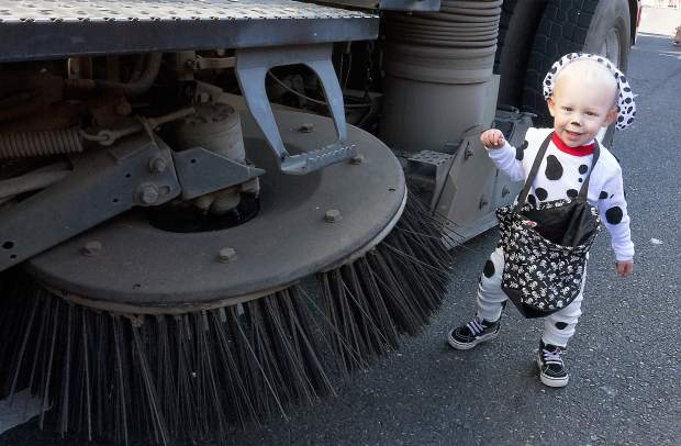 17-month-old Raleigh Schuster hangs out next to the City of Grass Valley's Street sweeper brush Tuesday in downtown Grass Valley.