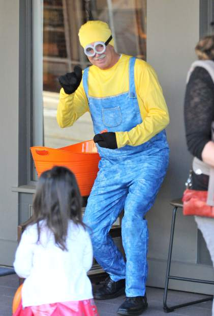 An adult Minion by the name of Alan Keeny hands out candy to children in front of Ashley Home Furniture's storefront in downtown Grass Valley.