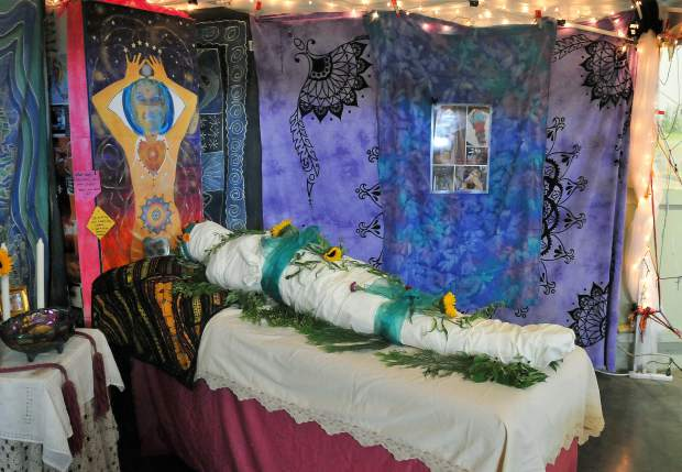 Full Circle Living and Dying Collective's altar shows an example of a shrouded dead body ready for cremation or burial.