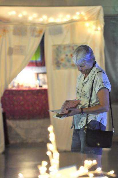 An altar goer reads along with an interpretive program while experiencing each altar at the Altar Show.