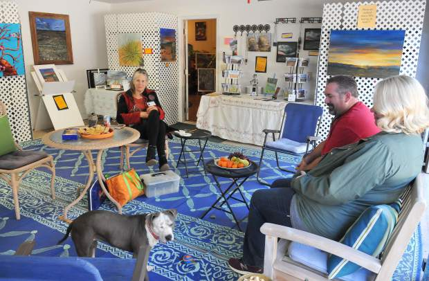 Grass Valley artist Valerie Messervy Birkhoff sits with visitors and her dog in her garage and artist space during Saturday's Open Studios and Art Tour in Western Nevada County.