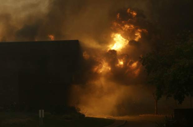 Smoke and fire rise from the Fountaingrove Inn Hotel as it burns in Santa Rosa, Calif., Monday, Oct. 9, 2017. Wildfires whipped by powerful winds swept through Northern California early Monday, sending residents on a headlong flight to safety through smoke and flames as homes burned. (AP Photo/Jeff Chiu)