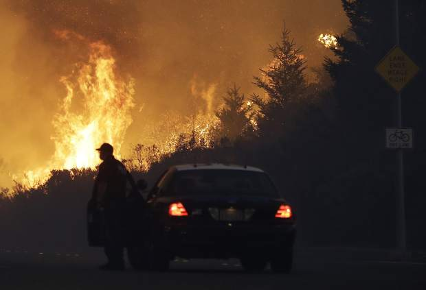 A law enforcement officer blocks a road as flames burn in a residential area in Santa Rosa, Calif., Monday, Oct. 9, 2017. Wildfires whipped by powerful winds swept through Northern California early Monday, sending residents on a headlong flight to safety through smoke and flames as homes burned. (AP Photo/Jeff Chiu)