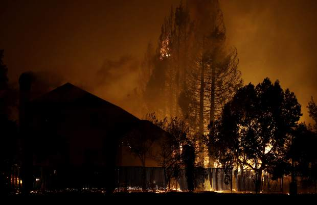 Trees burn behind houses in a residential area in Santa Rosa, Calif., Monday, Oct. 9, 2017. (AP Photo/Jeff Chiu)