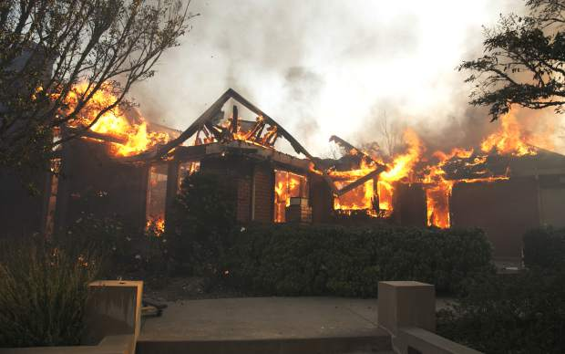 Flames from a wildfire consume a home Monday, Oct. 9, 2017, east of Napa, Calif. Wildfires whipped by powerful winds swept through Northern California early Monday, sending residents on a headlong flight to safety through smoke and flames as homes burned. (AP Photo/Rich Pedroncelli)