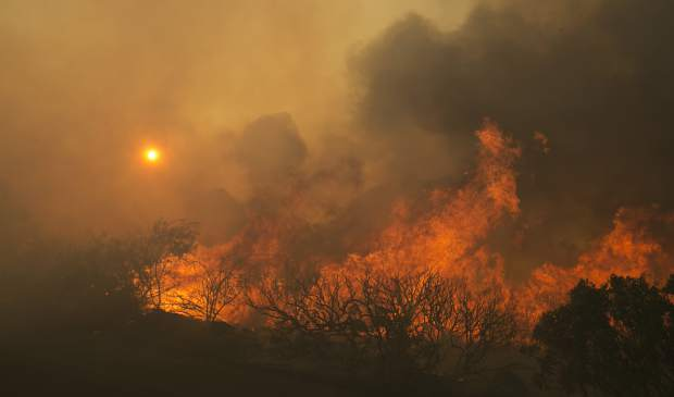 The sun rises as flames from a wildfire burn Monday, Oct. 9, 2017, east of Napa, Calif. The fire is one of several burning across Northern California's wine country. (AP Photo/Rich Pedroncelli)