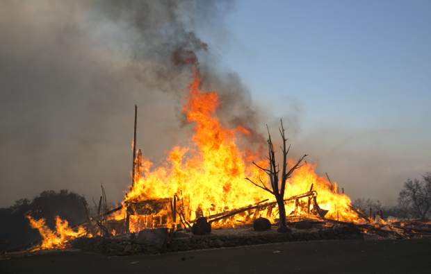 Flames from a wildfire consume a home Monday, Oct. 9, 2017, east of Napa, Calif. The fire is one of several burning across Northern California's wine country. (AP Photo/Rich Pedroncelli)