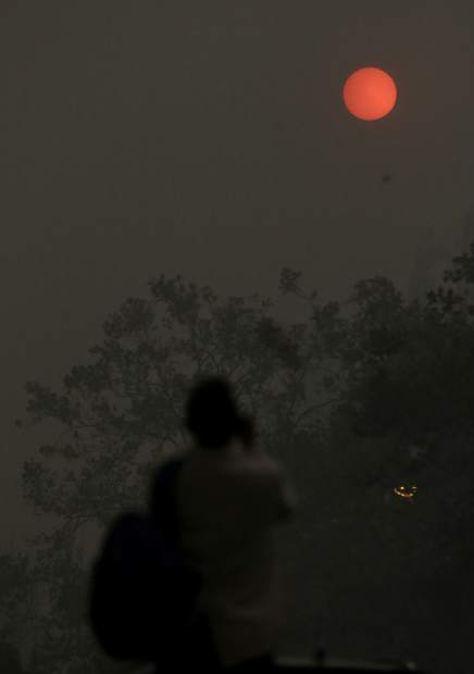 A woman takes a photo of the sun covered from smoke and haze from fires in Santa Rosa, Calif., Monday, Oct. 9, 2017. Wildfires whipped by powerful winds swept through Northern California early Monday, sending residents on a headlong flight to safety through smoke and flames as homes burned. (AP Photo/Jeff Chiu)