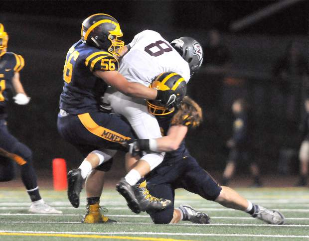 Nevada Union's Brendan Dipietro (56) and Justin Houlihan (20) take down Woodcreek's Maxton Page (8) during the Miners' loss to the Timberwolves.