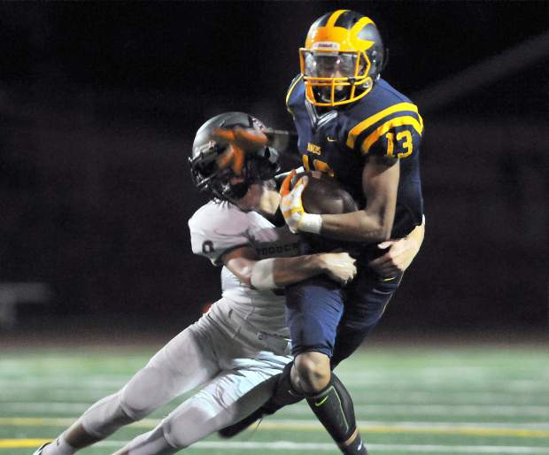 Nevada Union's Cameron Dallago (13) is pulled down by a Woodcreek defender.